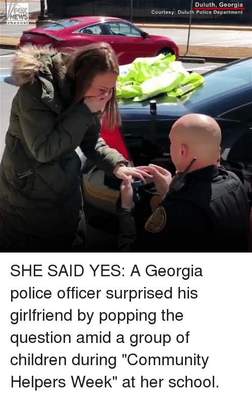 """Children, Community, and Memes: Duluth, Georgia  Courtesy: Duluth Police Department  WS SHE SAID YES: A Georgia police officer surprised his girlfriend by popping the question amid a group of children during """"Community Helpers Week"""" at her school."""