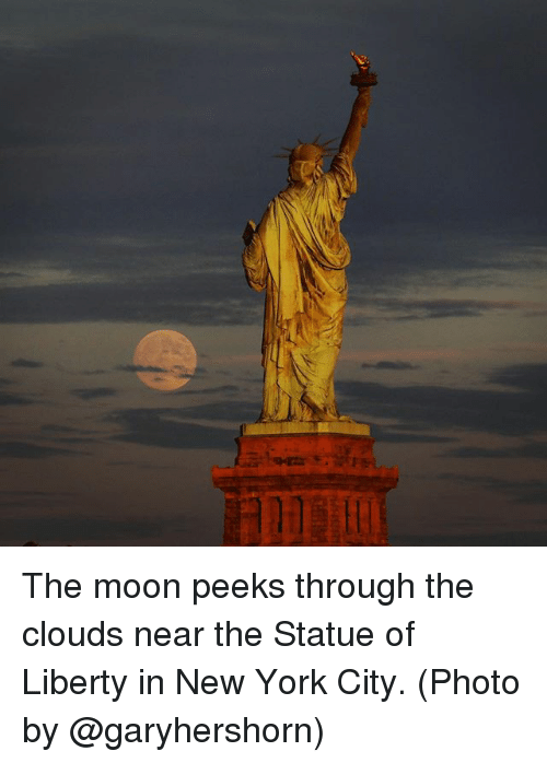 Memes, New York, and Moon: The moon peeks through the clouds near the Statue of Liberty in New York City. (Photo by @garyhershorn)