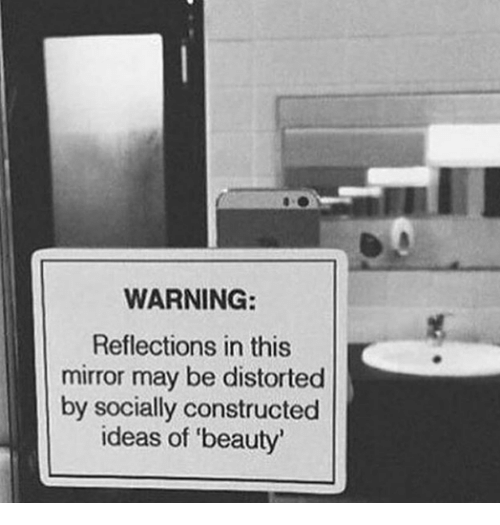 distorted: WARNING:  Reflections in this  mirror may be distorted  by socially constructed  ideas of 'beauty'
