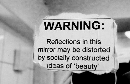 Mirror, Ideas, and May: WARNING:  Reflections in this  mirror may be distorted  by socially constructed  ideas of 'beaut